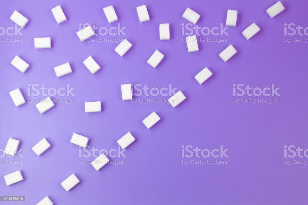 White sugar cubes arranged in diagonal lines on purple background....