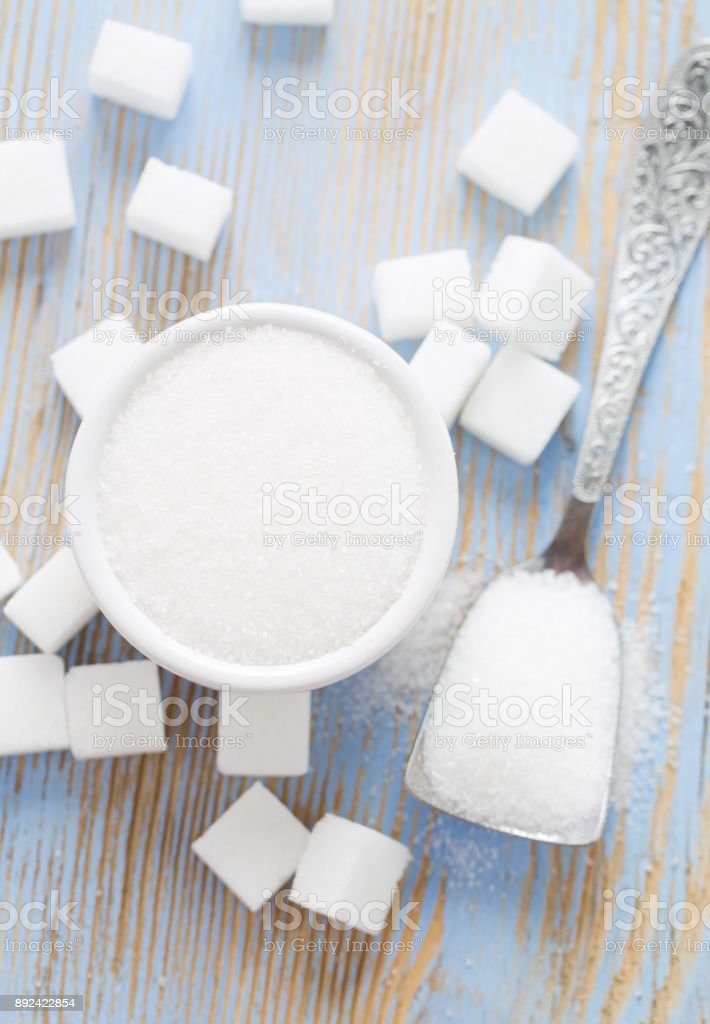 white sugar cubes on wooden surface stock photo