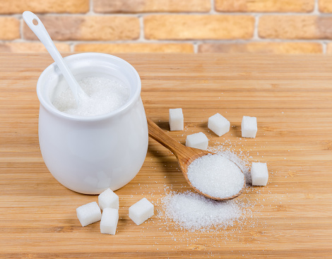 White sugar in sugar-bowl, wooden spoon and sugar cubes