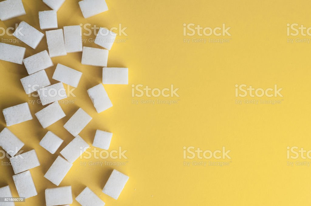 White sugar on yellow background. Cubes sugar with copy space. Top view or flat lay royalty-free stock photo