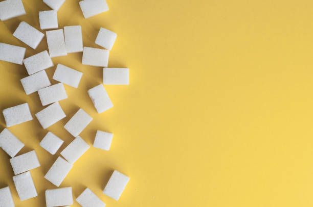 White sugar on yellow background. Cubes sugar with copy space. Top view or flat lay stock photo