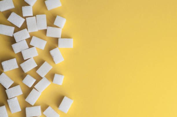 Sucre sur fond jaune blanc. Cubes de sucre avec l'espace de la copie. Vue de dessus ou lay plat - Photo