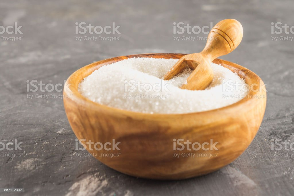 White sugar sugar in a wooden plate with a dustpan on a dark background. stock photo