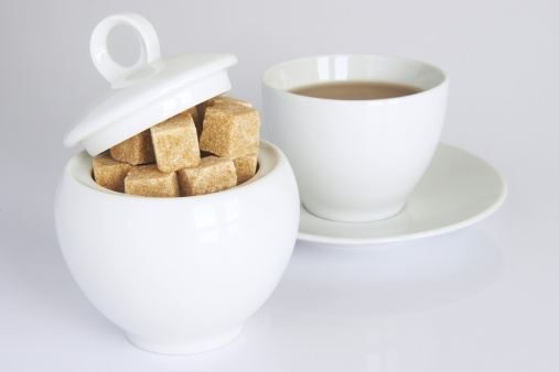 white sugarbowl with brown sugarcubes and a cup of tea