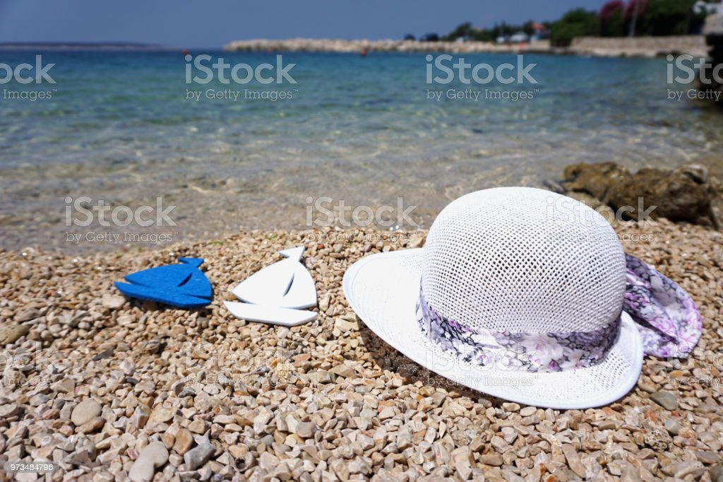 White summer hat and two boat toy on a pebble beach and blue sea in Croatian Island of Pag on a beautiful sunny day stock photo