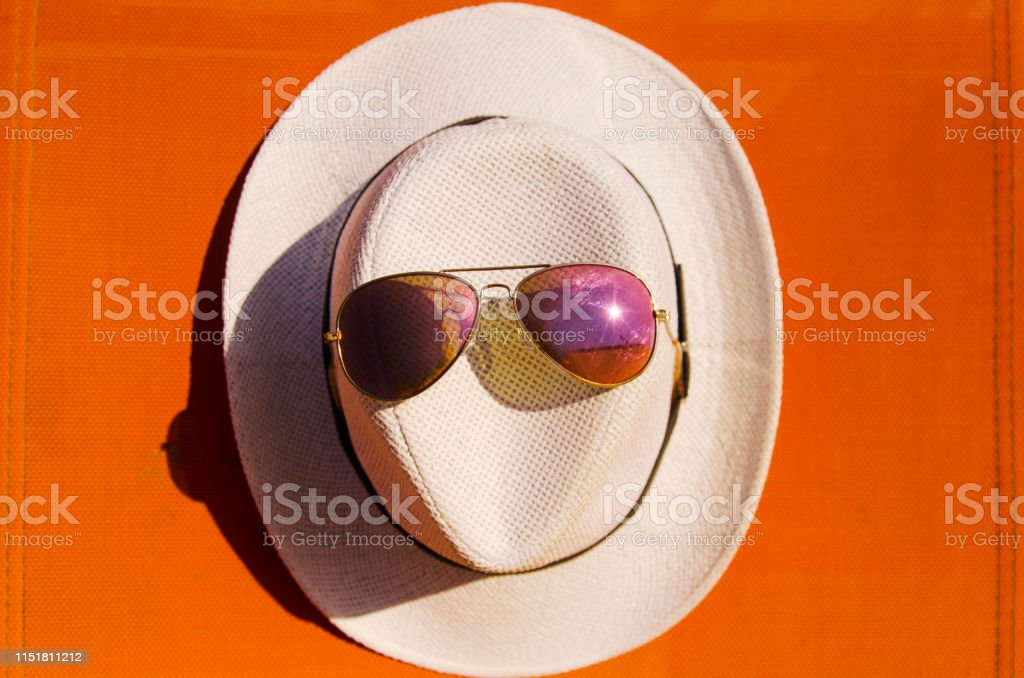 White sun hat with sun glasses on it,top view.Orange color background...