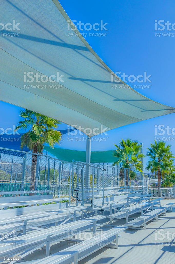 White sun shades hang over bleechers at sport area (P) stock photo