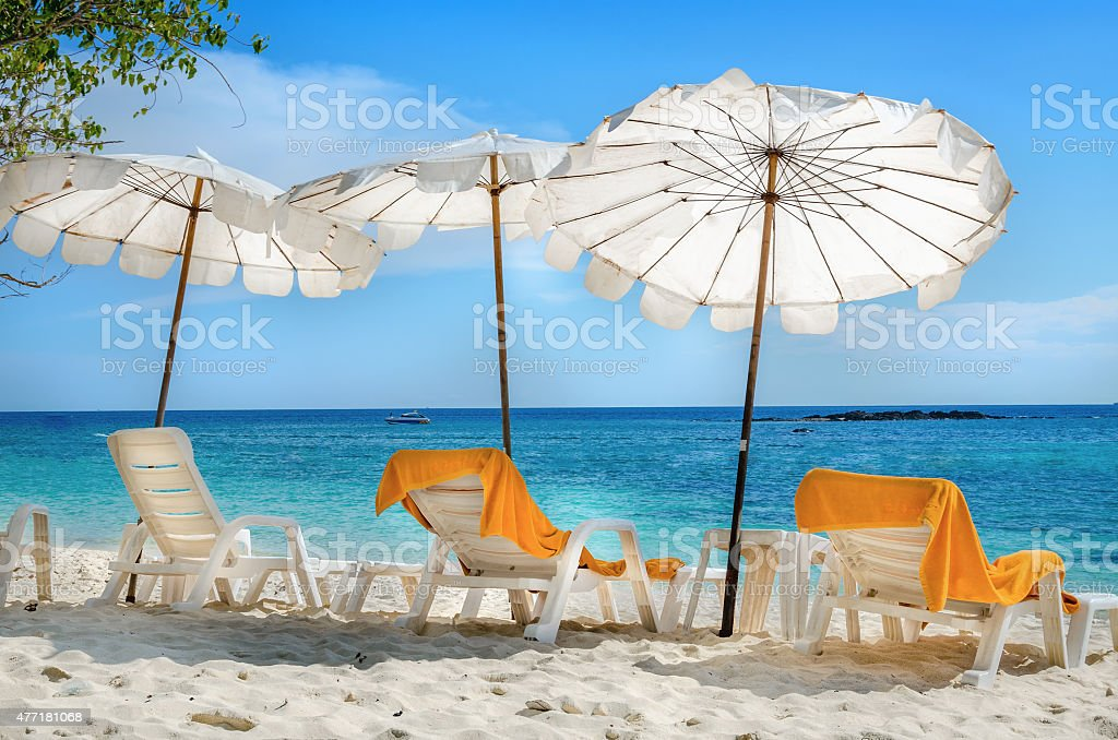White sunbeds and orange towels on sandy beach stock photo