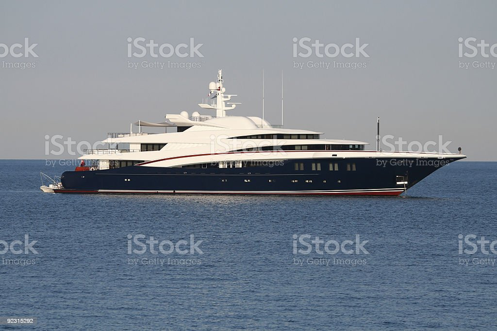 White Super yacht with blue hull and red stripe stock photo