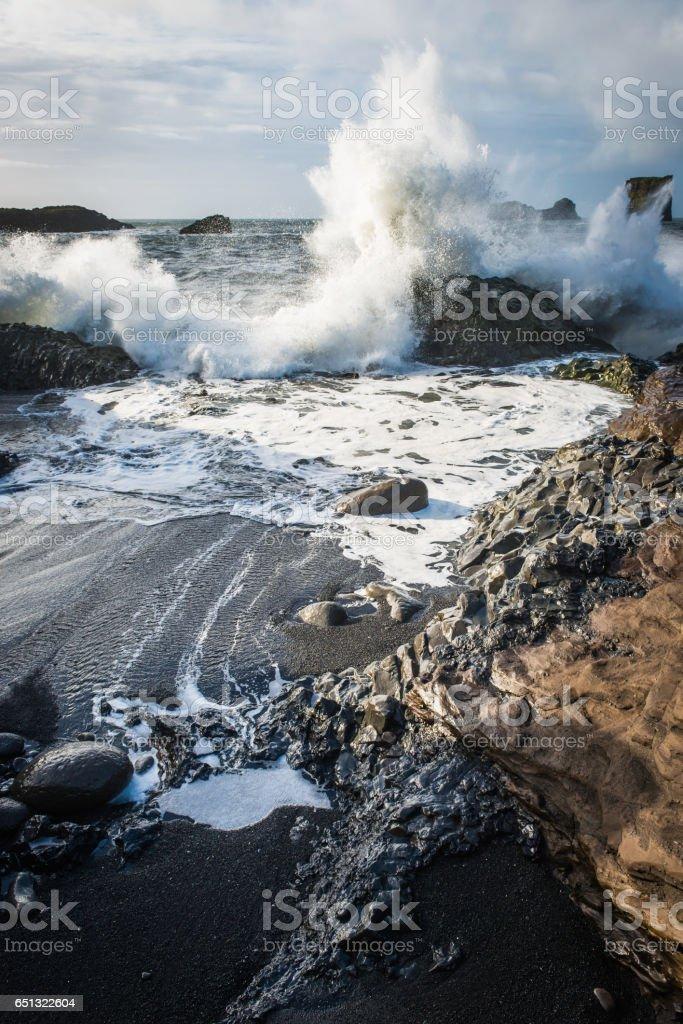 White surf and ocean waves crashing onto rocky shore Iceland stock photo