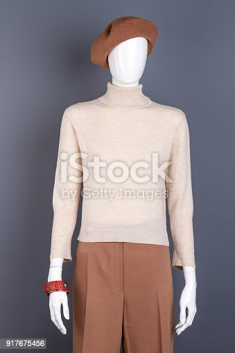 White sweater and brown trousers on mannequin. Dummy dressed in brown french beret. Women fashion look.