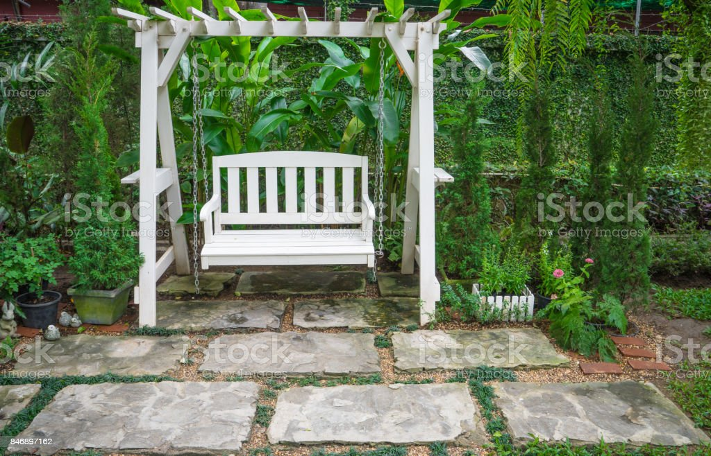 White Swing in a Garden. Concept of relaxation stock photo