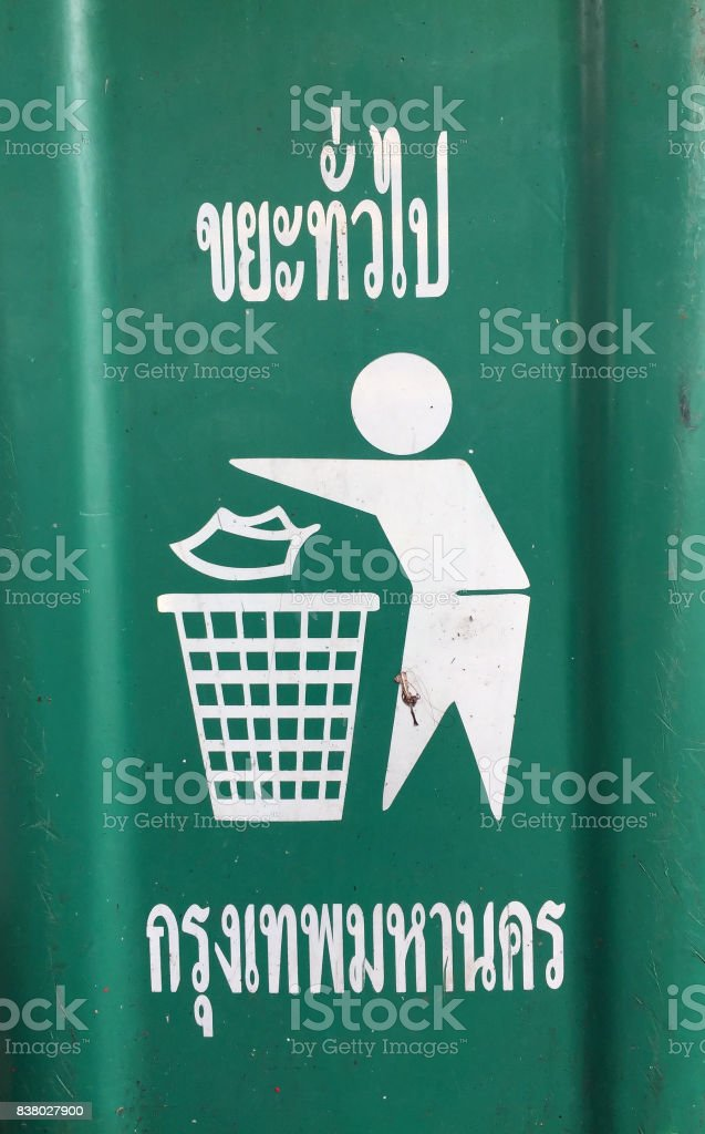 White symbol of human litter into the bin, on beside of the green plastic bin. stock photo