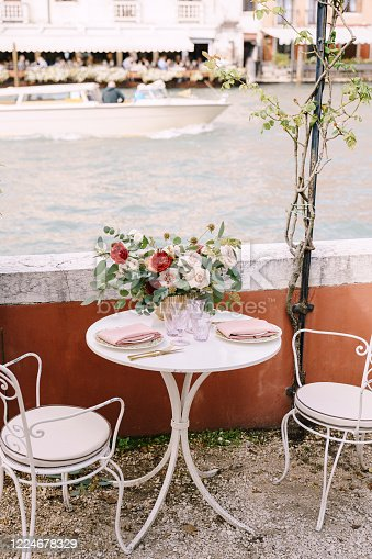 A white table and chairs for two, in a restaurant on the banks of the Grand Canal in Venice, Italy. On the table there is large bouquet of roses and leaves of eucalyptus, glasses, plates and cutlery