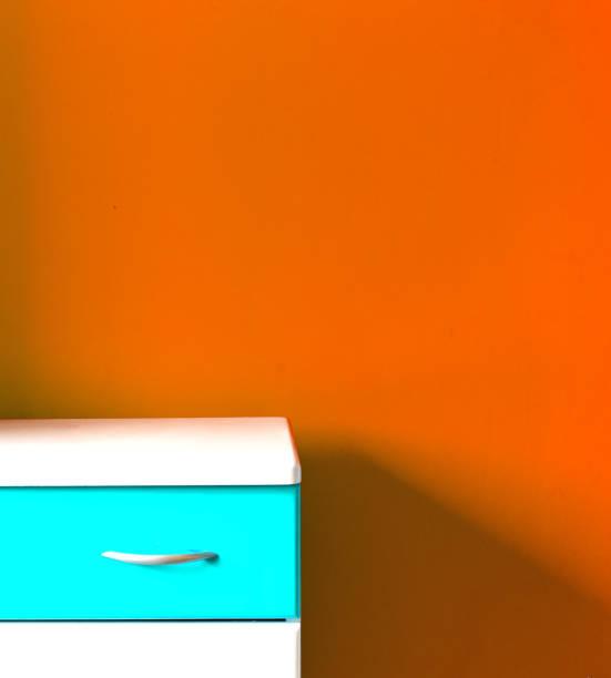 mesa blanca y pared naranja en el vivero - foto de stock