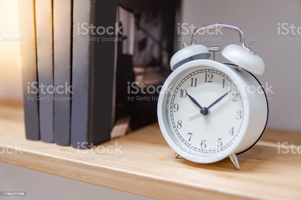 White Table Clock On Wooden Bookshelf Stock Photo Download Image Now Istock