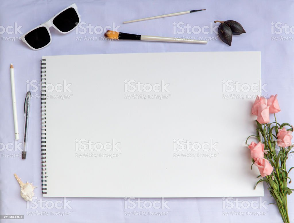 White table composition with art supplies, rose and blank watercolor paper page stock photo