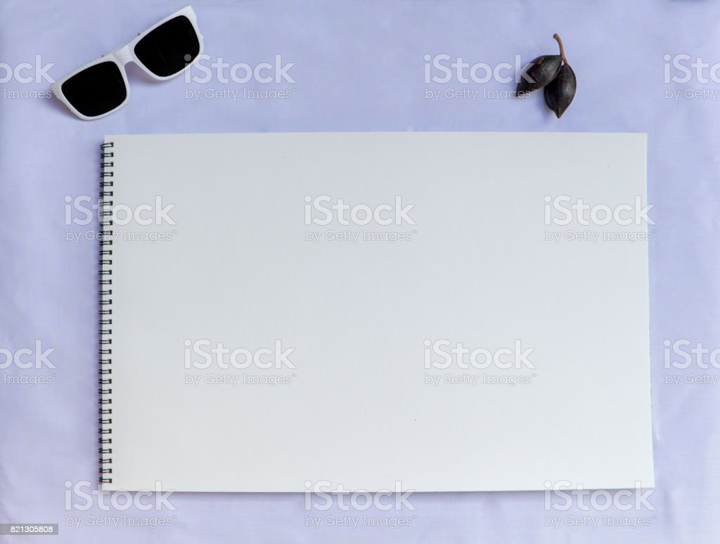 White table composition with rose and watercolor paper. stock photo