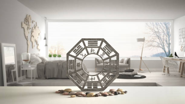 White table shelf with bagua and pebble stone, white scandinavian bedroom with big panoramic window, zen concept interior design, feng shui template idea background stock photo