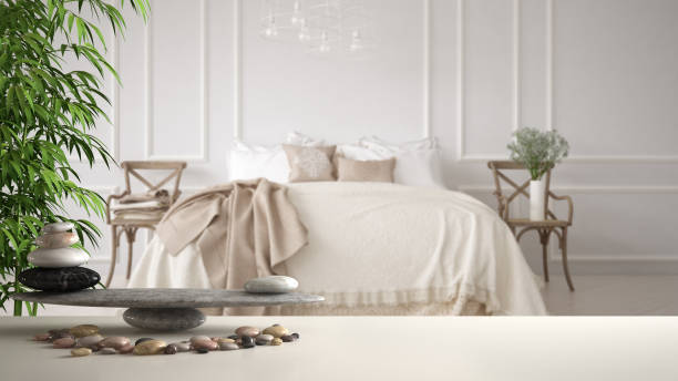 White table shelf with pebble balance and bamboo plant over vintage classic bedroom with soft bed full of pillows and blankets, zen concept interior design stock photo