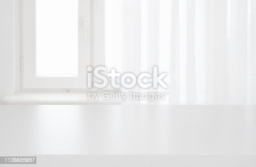 istock White table top on blurred pastel background of curtained window 1126635937