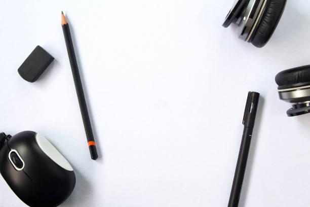 weiße tischansicht mit schwarzem stift und bleistift, schwarzen kopfhörern und computermaus. - pastellstifte stock-fotos und bilder
