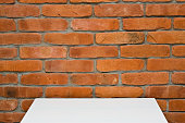 White table with red brick wall copy space