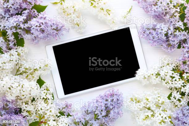 Photo of White tablet computer and lilac flowers on white wooden background. Top view
