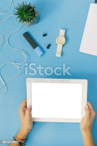 istock White tablet with blank screen in female hands on blue background, top view 921013320