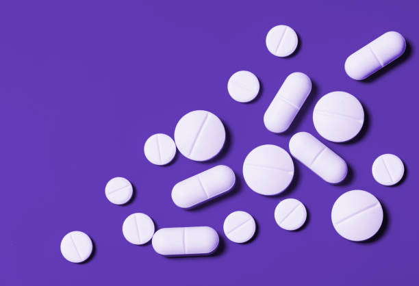 white tablets of different shapes on a bright violet background. Horizontal view from above. Close-up white tablets of different shapes on a bright violet background. Horizontal view from above. Close-up antipyretic stock pictures, royalty-free photos & images