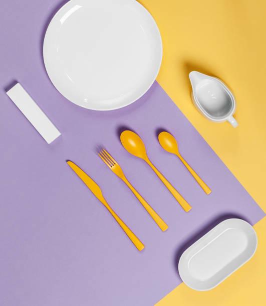 weißes geschirr und gelbe besteck auf pastell gelb-violetten hintergrund. - küche deko lila stock-fotos und bilder