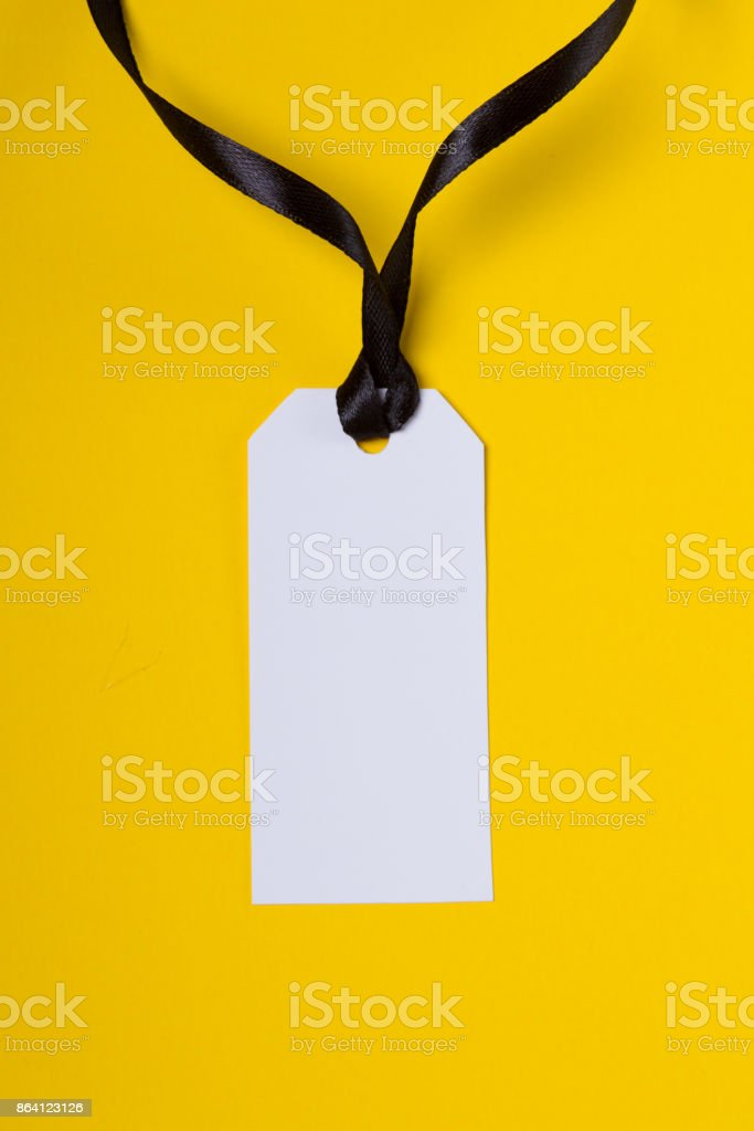 White tag with black ribbon on yellow background royalty-free stock photo