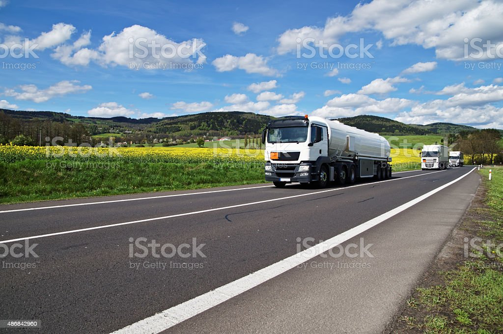 White tanker and trucks driving along the asphalt road stock photo