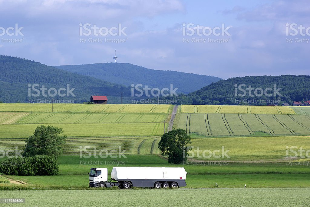 White tanker on the road between some fields royalty-free stock photo