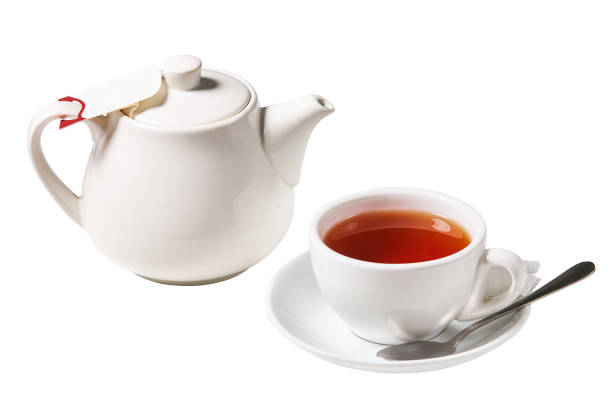 White tea cup with a spoon and a kettle White tea cup with a spoon and a kettle (tea pot) isolated on white background teapot stock pictures, royalty-free photos & images