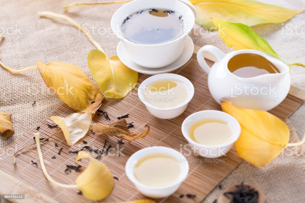 White tea cups and autumn leaves on the table. Autumn tea. royalty-free stock photo