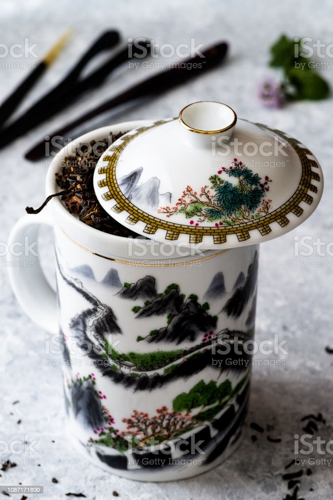 White teapot with 'great wall' design, tea herb, delicate background - foto stock