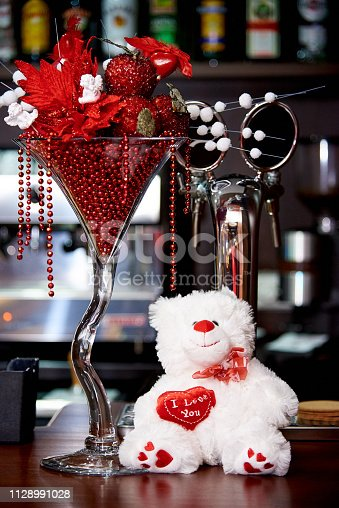 istock White teddy bear on the bar with decoration for the holiday. 1128991028