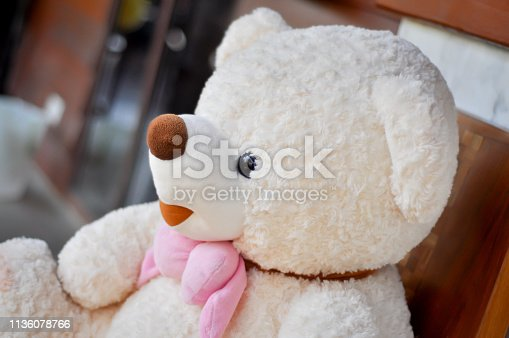 White teddy bear tied with pink scarf.