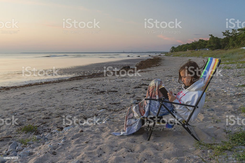 White teenager sitting on a beach and reading stock photo