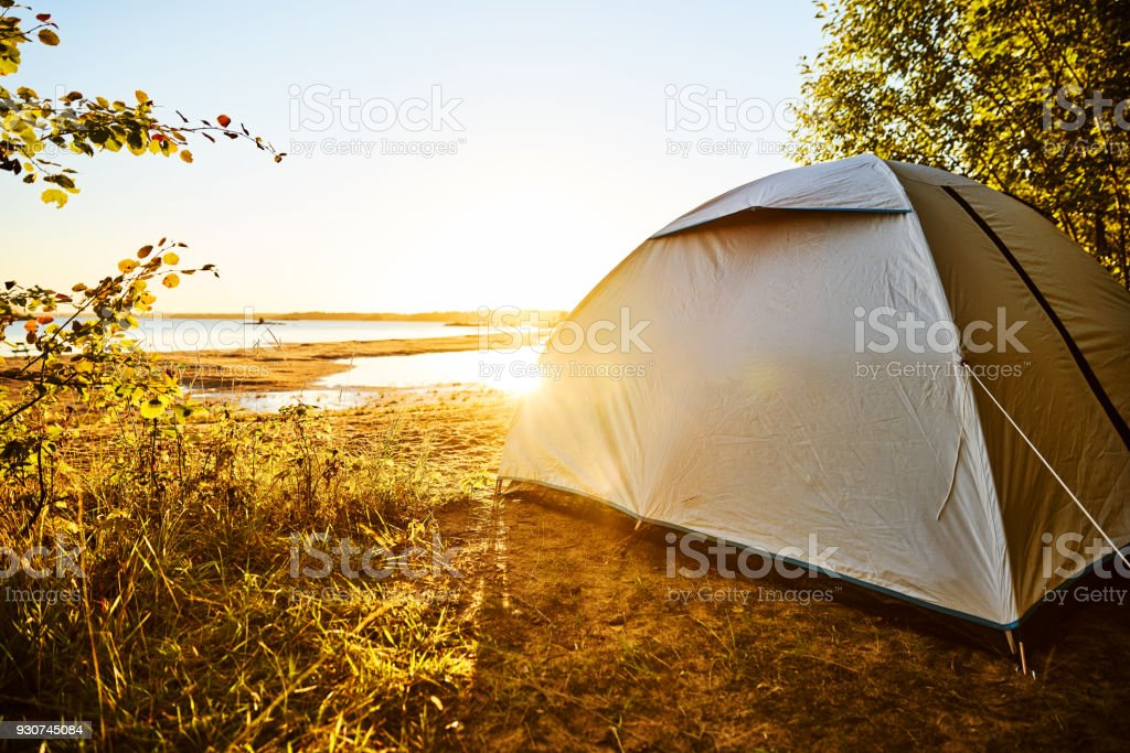 White tent standing at a beach camping spot at lake Vänern in Sweden. The sun is shining and soon will be sunset. Tent is standing on the right side covered by trees  and plants. Water reflections. stock photo