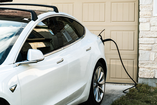 Austin , Texas , uSA - 2-1-2021: Tesla Model 3 charging at home in front of the house on the L2 at home charging that is provided with every Tesla vehicle