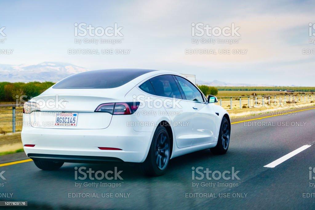 Tesla Model 3 bianca in autostrada - Foto stock royalty-free di Ambientazione esterna