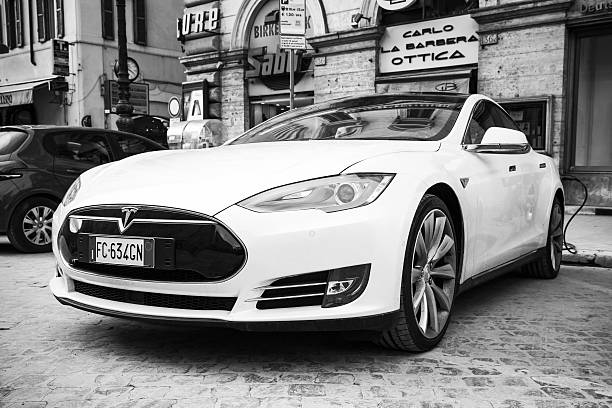 White Tesla model S car parked on roadside Rome, Italy - February 13, 2016 : White Tesla model S car parked on urban roadside in Rome, front view, close-up black and white photo tesla motors stock pictures, royalty-free photos & images