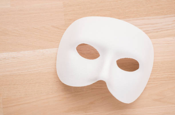 white theatre or carnival mask on wooden table - dramatisches theater stock-fotos und bilder