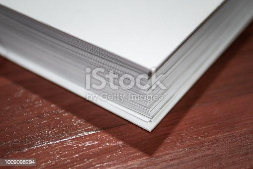 istock White thick book on wooden background 1009098294