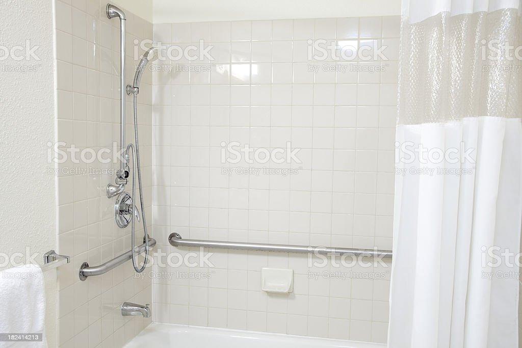 Bagno con piastrelle bianche e vasca da bagno con maniglioni per