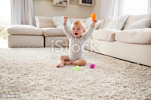 istock White toddler boy on the floor in sitting room raising arms 947849742