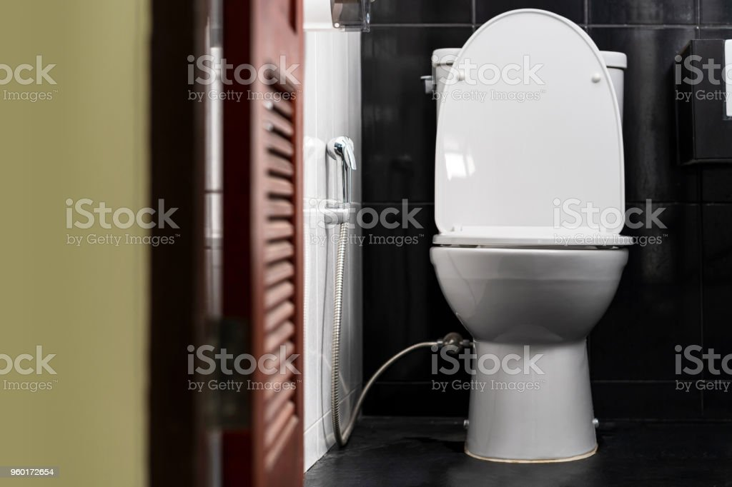 White toilet bowl in a bathroom of a private home stock photo