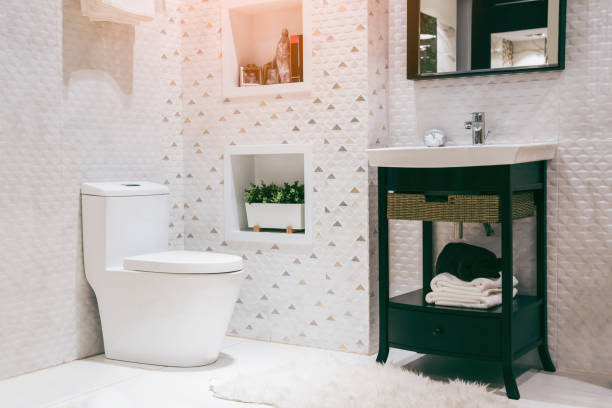 White toilet bowl in the bathroom with shower tiles and comfortable. stock photo